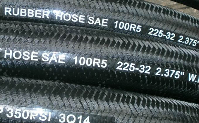 Several SAE 100 R5 steel wire reinforced hydraulic hoses are on the floor.