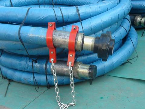 two rolls of rotary drilling hoses wrapped with blue package paper are on the ground.